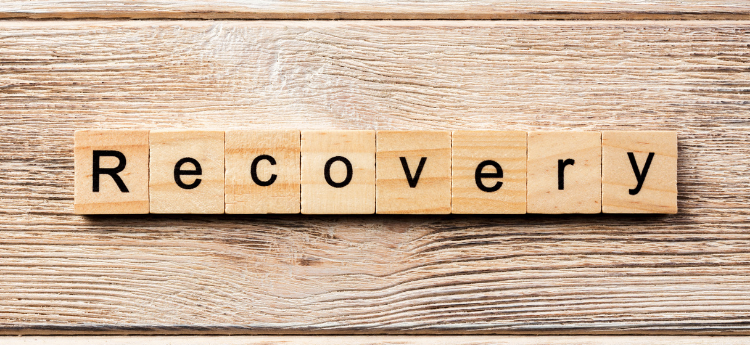 Wooden Scrabble like tiles spelling out the word RECOVERY